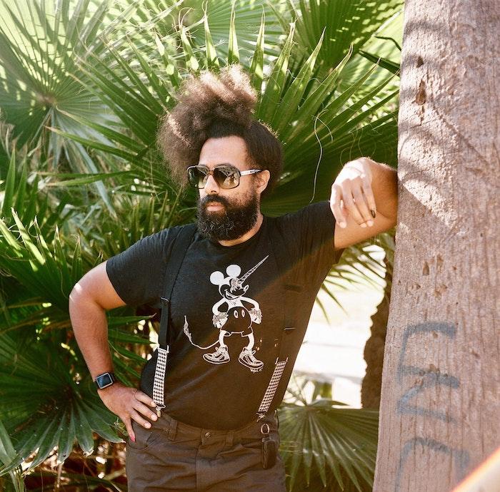 Reggie Watts leaning on a tree